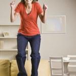 Teenage girl jumping on sofa — Stock Photo