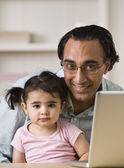 Smiling Father With Daughter Sitting By Laptop — Photo