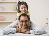 Girl Sitting on Fathers Back — Stockfoto