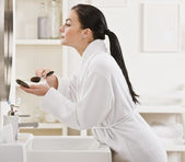 Mujer poniéndose maquillaje — Foto de Stock