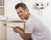 Smiling Man Fixing Cabinet Door — Stock Photo