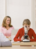 Student looking into microscope in classroom — Stock Photo