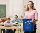 Teacher holding recycling bin — Stock Photo
