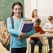 Student carrying backpack and books — Stock Photo
