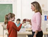 Student giving teacher apple — Stock Photo