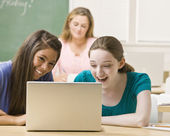 Students sharing laptop in classroom — Stock Photo