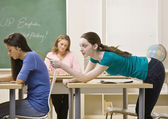 Student tapping classmate in classroom — Stock Photo