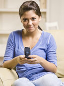Teenage girl text messaging on cell phone — Stock Photo