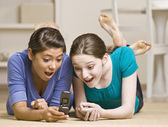 Teenage girls text messaging on cell phone — Stock Photo