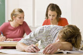 Student sleeping at desk in classroom — Stock Photo