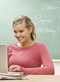 Student typing on laptop in classroom — Stock Photo