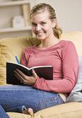 Teenager-Mädchen in Buch schreiben — Stockfoto