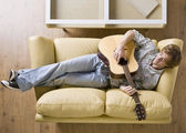 Man laying on sofa playing guitar — Stock Photo