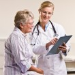 Doctor explaining medical chart to senior woman — ストック写真