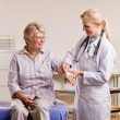 Stock Photo: Doctor adjusting senior womwrist splint