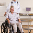 Senior woman sitting in wheelchair with doctor — Stock Photo