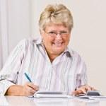 Çek yazmaya kadın kıdemli — Stok fotoğraf