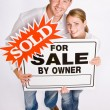 Couple holding for sale sign — Stock Photo