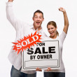 Couple cheering and holding for sale sign — Stock Photo #18794335