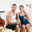 Man and woman drinking water in health club - Stock Photo