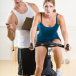 Stock Photo: Trainer timing woman on stationary bicycle