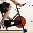 Mriding stationary bicycle in health club — Stock Photo #18794845