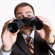 Businessman looking through binoculars — Stock Photo