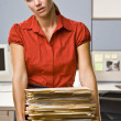 Businesswoman carrying stack of file folders — Stock Photo