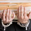 Foto de Stock  : Businessmin handcuffs holding file folders
