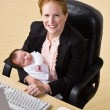 Businesswoman holding baby at desk - Stock Photo