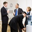 Business drinking water at water cooler — Stock Photo