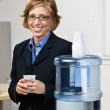 Businesswoman getting water from water cooler — Stock Photo #18799527
