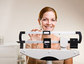 Woman weighing herself in doctor office — Stock Photo