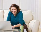 Senior woman using laptop in livingroom — Stock Photo