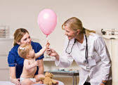 Doctor handing baby girl balloon — Stock Photo