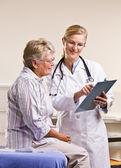 年配の女性にカルテを説明する医者します。 — ストック写真