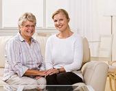 高级女人和女儿在客厅坐 — 图库照片