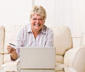 Woman using creditcard to buy internet merchandise — Stock Photo