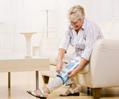Senior woman adjusting knee brace — Stock Photo