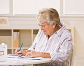 Senior woman writing checks — Stock Photo