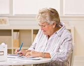 Senior woman writing checks — Stock Photo