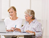 Senior woman writing checks with daughter help — Stock Photo