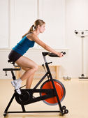 Woman riding stationary bicycle in health club — 图库照片