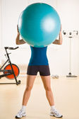 Woman holding exercise ball in health club — Stock Photo