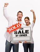 Couple cheering and holding for sale sign — Stock Photo