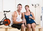 Man and woman drinking water in health club — Stok fotoğraf