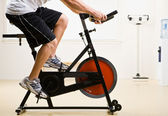 Man riding stationary bicycle in health club — Stock Photo