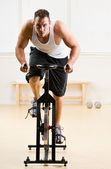 Man riding stationary bicycle in health club — 图库照片