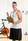 Personal trainer holding stop watch and clipboard — Stock Photo