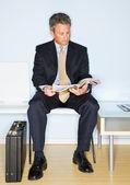 Businessman reading magazine in waiting room — Stock Photo